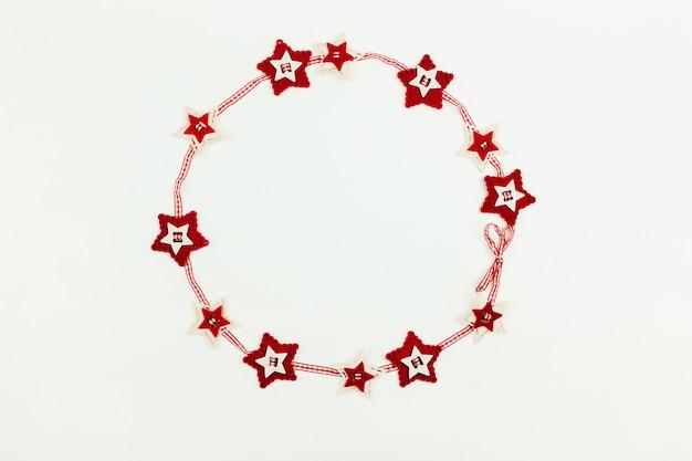 Новогодний фон с красным венком из звезд.