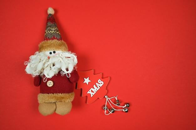 Новогодний фон со скандинавским гномом и деревянной елкой на красном фоне