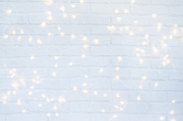 Christmas background with shining lights. white brick wall.