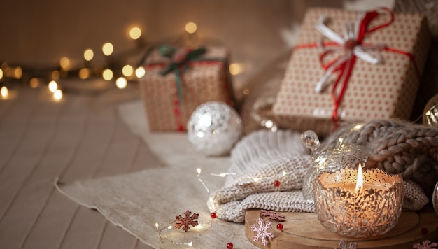 Christmas background with silver decorative burning candle, lights and gift boxes on a blurred background. copy space.
