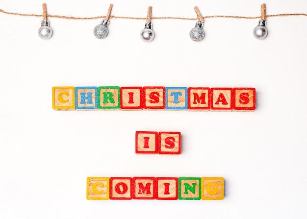 雪片、装飾、「クリスマスが来ています」の碑文とクリスマスの背景
