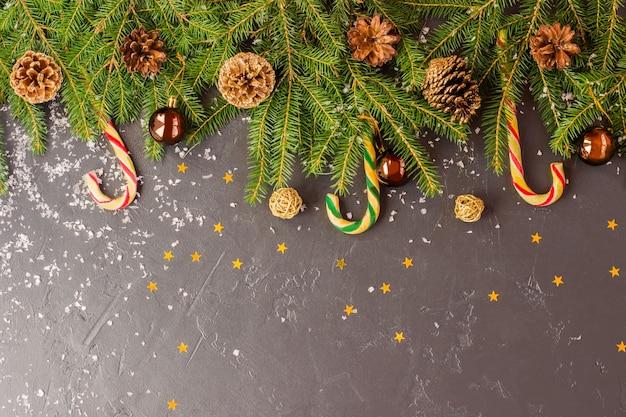 텍스트에 대 한 공간을 가진 크리스마스 배경입니다. 녹색 가지에는 황금색과 숲의 원뿔, 막대 사탕, 공, 별이 있습니다. 텍스트를 위한 공간입니다.