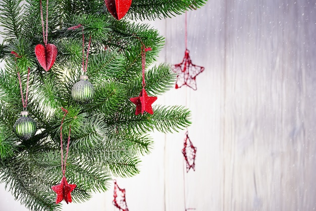 Christmas background with a spruce branch, red and green decorations and falling snow.