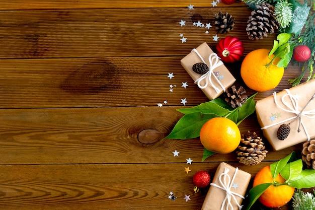 Новогодний фон с мандаринами, подарочные коробки, шишки, зимние украшения