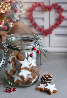 Christmas background with tasty star ginger cookies in a glass jar