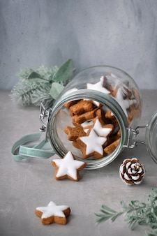 冬の花飾り付きのガラスの瓶においしいスタージンジャークッキーとクリスマスの背景