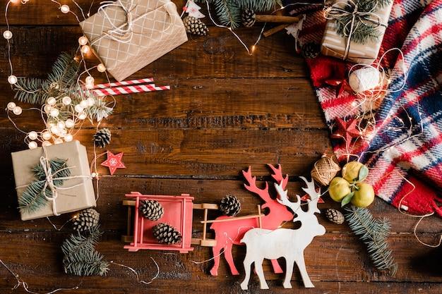 Новогодний фон с игрушечным оленем и санями, подарочными коробками, сосновыми шишками, хвойными деревьями, гирляндами и украшениями на деревянном столе