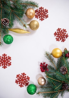 Новогодний фон с игрушками из веток деревьев и декоративными снежинками