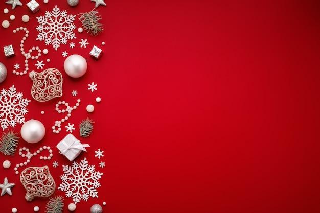 Новогодний фон с белыми украшениями граничит на красной копии пространства.