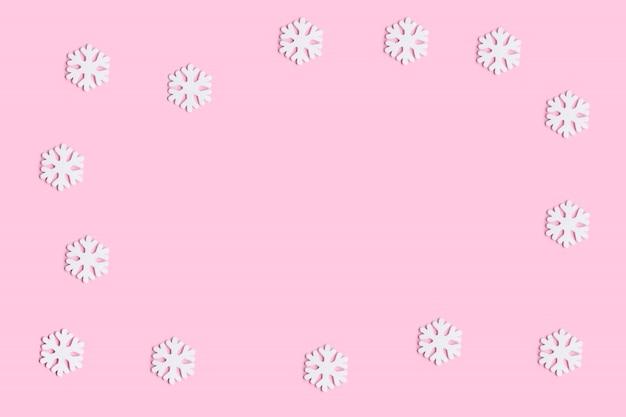 Новогодний фон с белыми снежинками украшения на розовом фоне