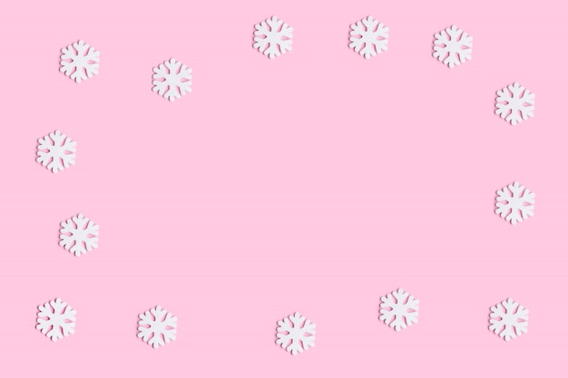Christmas background with white snowflakes decoration on a pink background