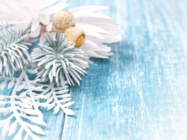 Christmas background with white spruce branches and snowflakes on a blue wooden background