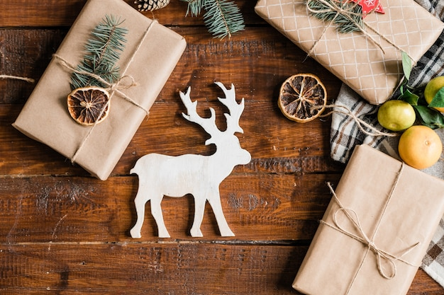 Christmas background with white toy deer, packed giftboxes, clementines and decorations on table