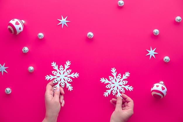 白い装身具、おもちゃ、鮮やかな明るいピンクの紙の上のクリスマスの装飾とクリスマスの背景。 2つの木製の雪片を保持している手。