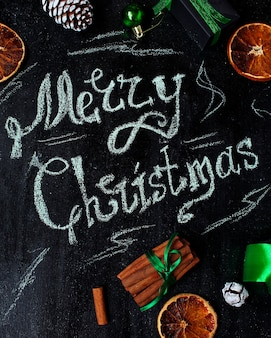 Christmas background with the words merry christmas,  dry orange, white pinecone, green christmas tree balls