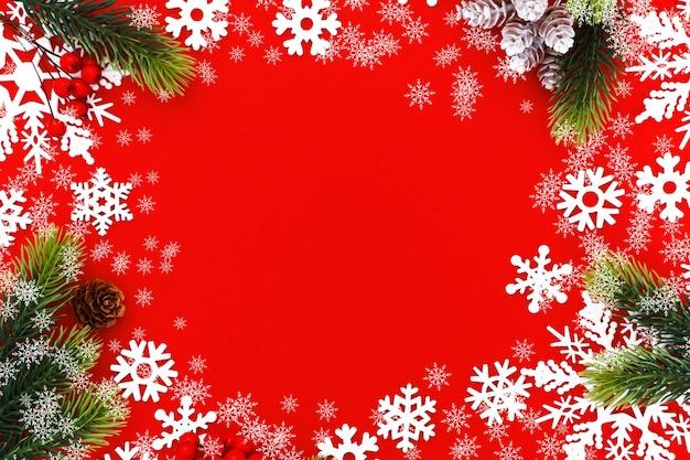 赤いキャンバスの背景にクリスマスツリーの枝と雪片とクリスマスの背景。メリークリスマスカード。明けましておめでとうございます。