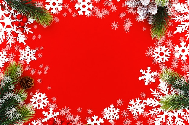 Christmas background with xmas tree branches and snowflakes on red canvas background. merry christmas card. happy new year.