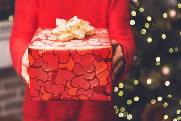 クリスマスの背景クリスマスや新年の装飾が施されたギフトボックスを保持している女性の手