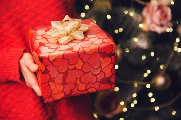 Рождественский фон женские руки, держащие рождественскую или новогоднюю подарочную коробку