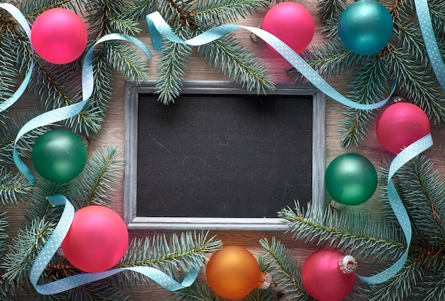 Christmas background on wood with blackboard, fir twigs, colorful trinkets and ribbons