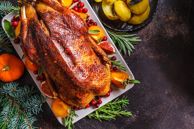 Christmas baked duck with herbs and fruits on gray plate on white background