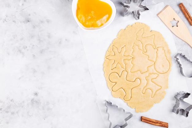 Рождественская выпечка. выпечка имбирных пряников, нарезка печенья из пряничного теста. вид сверху