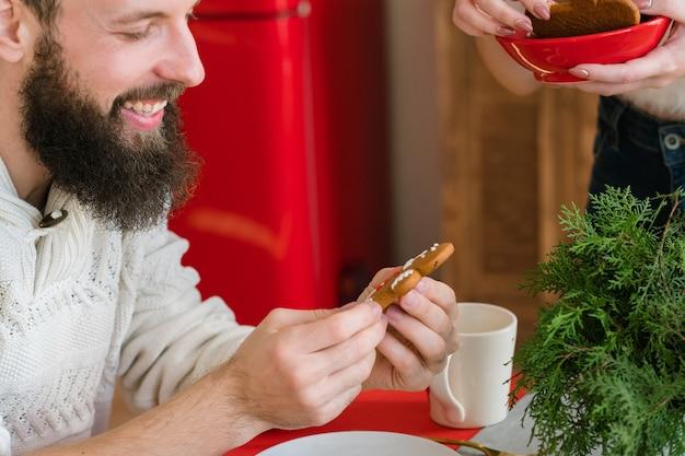 Рождественская выпечка. счастливый бородатый парень, держа печенье пряничный человечек, сделанный его женой, улыбаясь.