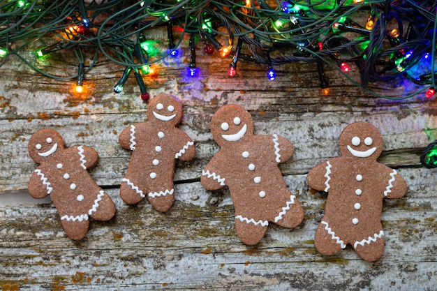 Christmas bakery and gingerbreads cookies with colorful lights top view on wooden table