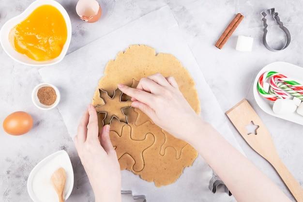 Рождественская выпечка. женщина, делающая имбирные пряники, резка печенья из пряничного теста.