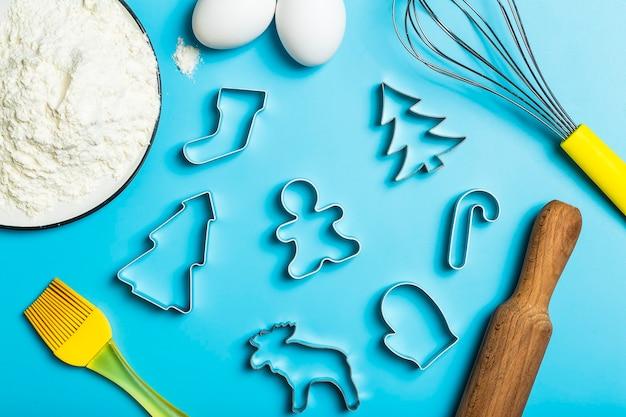 クリスマスのベーキングの背景クリスマスのクッキーカッターは、キッチンのベーキングテーブルのお祝いの食べ物にカビを作ります..。
