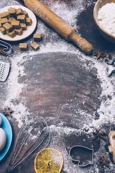 クリスマスのベーキングの背景。暗い背景にクリスマスベーキング(小麦粉、卵、砂糖、スパイス)を調理するための材料。コピースペース。クリスマス気分。