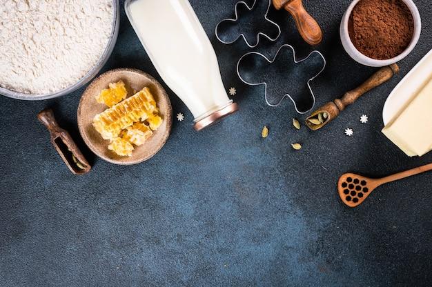 Рождественский фон выпечки. ингредиенты для приготовления рождественской выпечки на темном фоне. вид сверху с копией пространства. пряники. выпечка имбирного печенья. сырая лепешка для печенья