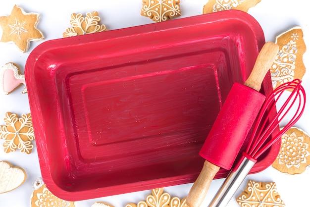 クリスマスのベーキングの背景。冬休みの準備、クリスマスセールシンプルフラットレイ。赤い天板、めん棒、伝統的な自家製ジンジャーブレッドと泡立て器、白い背景の上面図