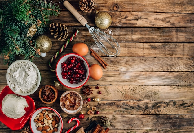 Christmas - baking cake background. dough ingredients and decorations on rustic wooden table