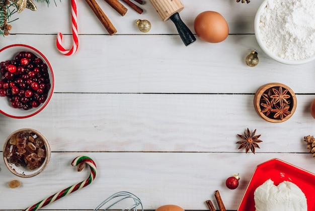 Christmas - baking cake background. dough ingredients and decorations on white wooden table