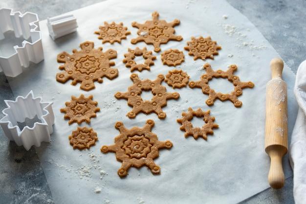 クリスマスのベーキングクッキーの雪片の形。生の生地、クッキーカッター、めん棒。抽象的な冬の食べ物の背景。