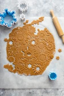 クリスマスのベーキングクッキーの雪片の形。生の生地、クッキーカッター、めん棒。