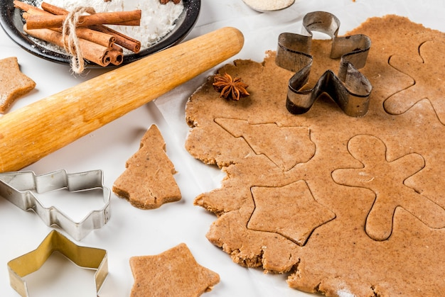 Christmas baking. ginger dough for gingerbread, gingerbread men, stars, christmas trees, rolling pin, spices (cinnamon and anise), flour. on the home kitchen white marble table. copy space