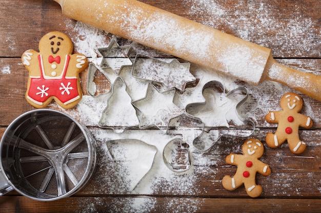 Рождественская выпечка. пряники и кухонная утварь на деревянном столе, вид сверху
