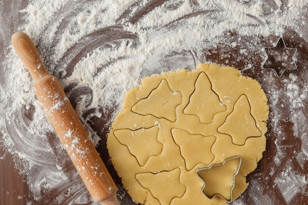 Christmas baking ingredients and tolls for dough preparation. flour, eggs, rolling pin and cookie cutters