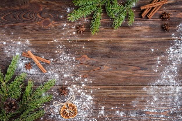 Рождественская выпечка имбирного печенья на темном деревянном фоне с еловыми ветками.