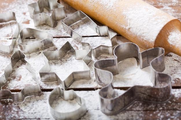 Рождественская выпечка. формы для пряников и кухонной утвари на деревянном столе