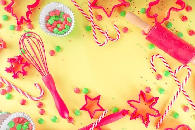 クリスマスのベーキング用品と材料。お祝いのクリスマスの甘いクッキー、ケーキを作るための道具やアクセサリーを備えた菓子屋またはパン屋の職場。上の明るい黄色の背景コピースペース
