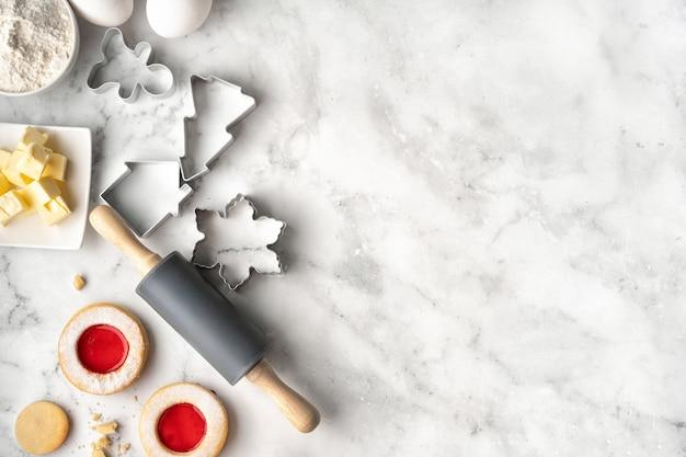 Рождественская выпечка с ингредиентами для приготовления печенья на белом мраморном фоне. копировать пространство