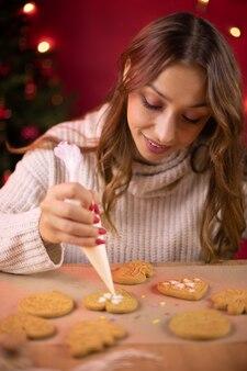 Мастерская рождественской выпечки. молодая красивая женщина делает рождественское печенье пряников, украшает праздничную пекарню глазурью из кондитерского мешка. новогодняя сезонная традиция. ремесло рецепты десертов концепция