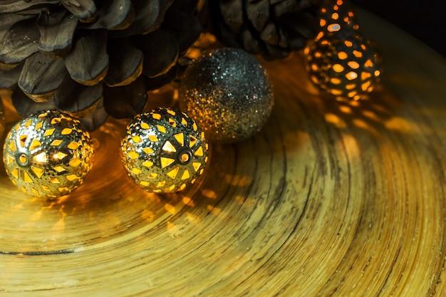 木の背景にクリスマスボールと松のコーン。