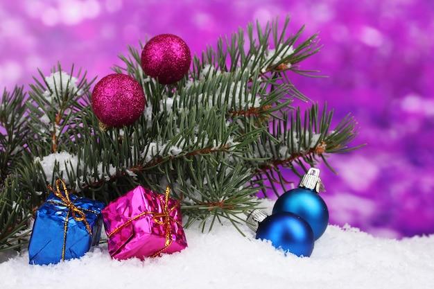 紫の雪の中で緑の木とクリスマスボールとおもちゃ