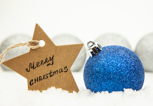 Christmas ball in blue on white snow and a star with the inscription merry christmas