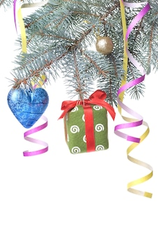 Christmas ball, gift and decoration on fir tree branch isolated on white
