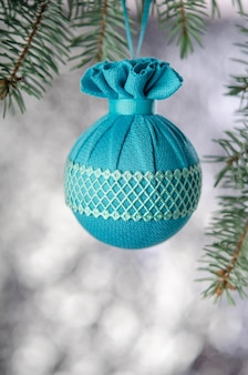 Christmas ball hanging on fir branch on silver background new year decoration
